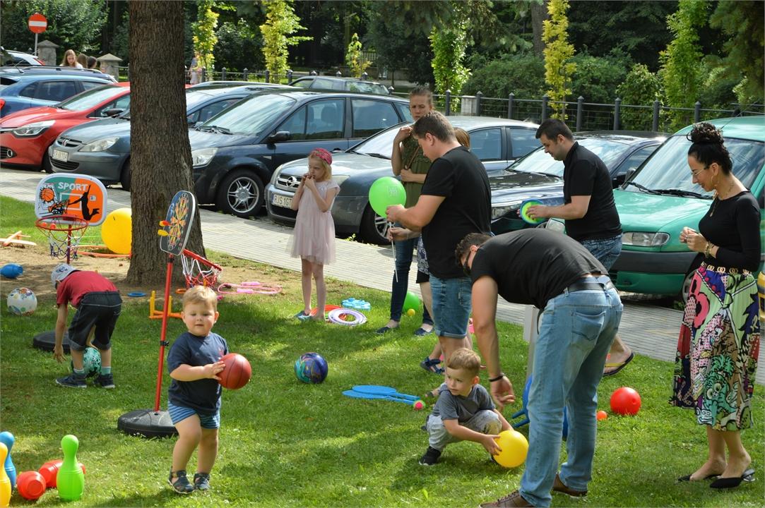 Dzieci bawią się piłkami na terenie zielonym przy Jasielskim Domu Kultury.