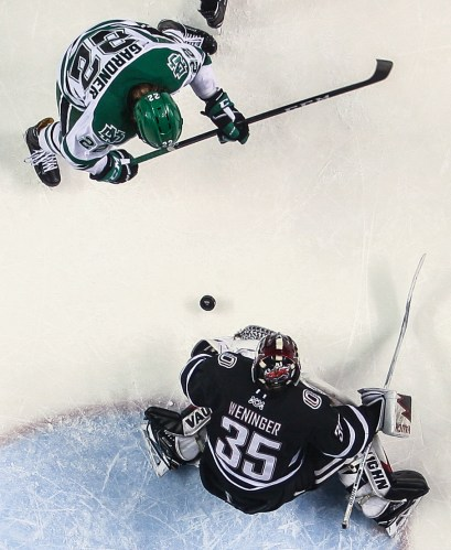 Omaha's Evan Weninger, goes to grab the puck as UND's Rhett Gardner tries to complete the play during a matchup at the Ralph Engelstad Arena in Grand Forks on Saturday, February 25, 2017.