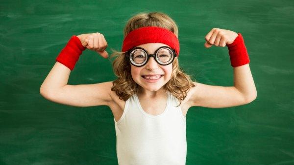 Schoolgirl in gym flexing her muscles