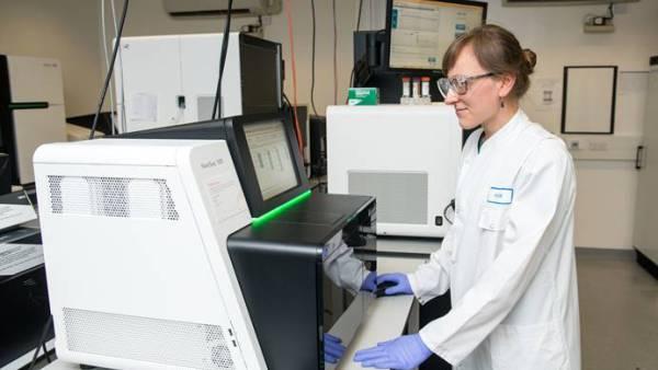 Scientist standing next to sequencer
