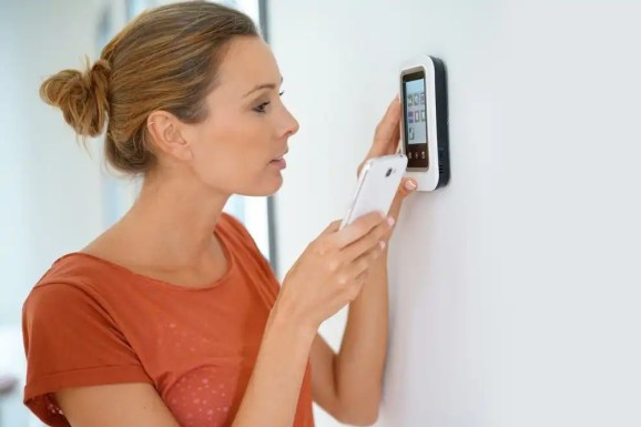 women programming a smart thermostat