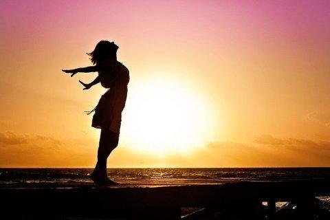 Femme les bras en arrière s'offrant au coucher du soleil
