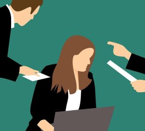 Dire non sans culpabilité - Femme travaillant sur ordinateur recevant des instructions de deux personnes