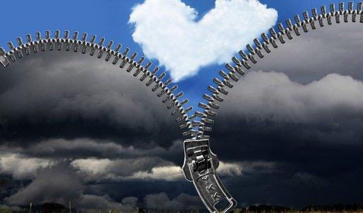 Paysage noir qui s'ouvre sur un ciel bleu et un nuage en coeur grâce à une fermeture éclair