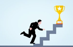 Relever un défi étapes par étapes - homme d'affaires montant des marches jusqu'à un trophée