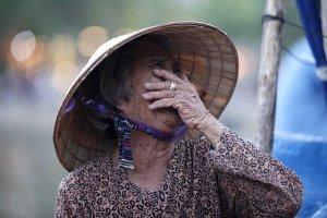 Femme asiatique en train de rire tout en couvrant sa bouche