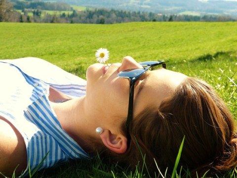 carpe diem et instant présent - jeune femme une fleur à la bouche allongée dans l'herbe