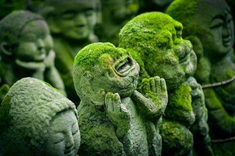 Statues de Kyoto (Japon) couvertes de mousse. L'une d'elle semble sourire et a les bras levés.
