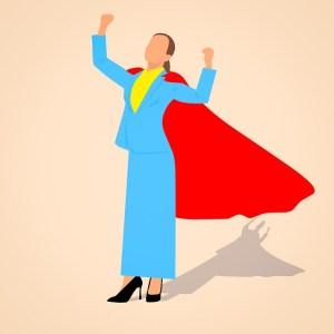 Vaincre le syndrome de l'imposteur - femme d'affaire levant les bras en l'air et portant une cape rouge