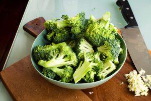 Chopped broccoli in a light blue bowl on a wood cutting board.