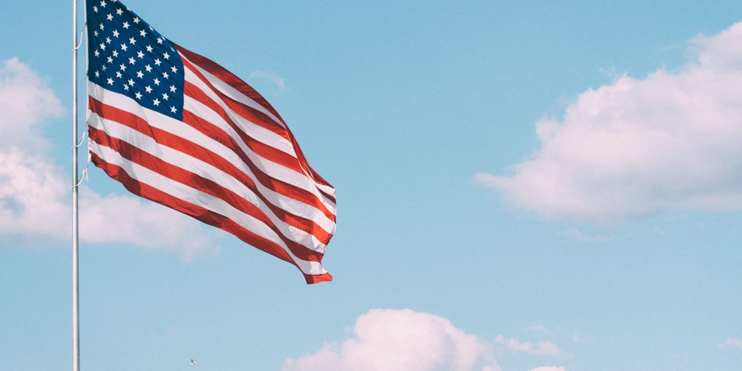 America flag flowing in the wind with a blue sky and white clouds in the background.