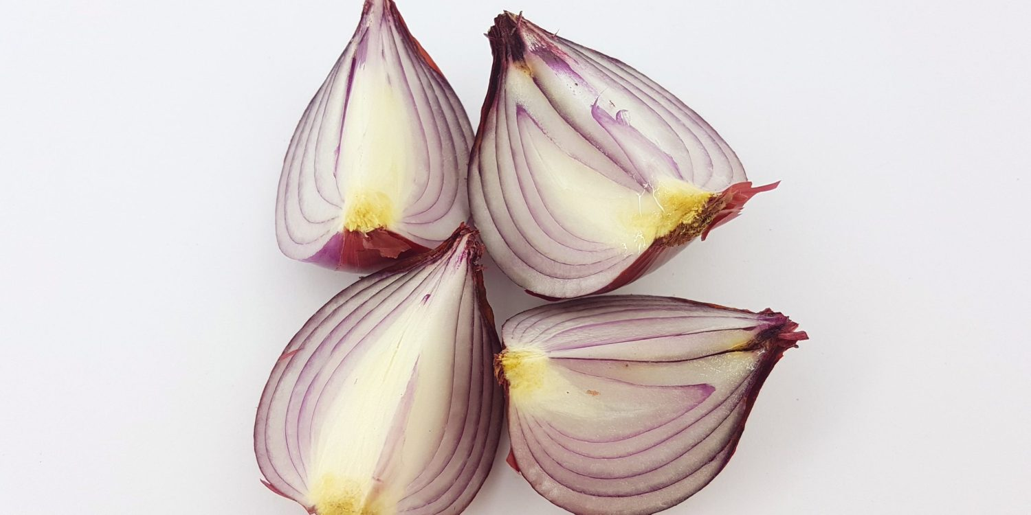 2 cloves of purple garlic cut in half on a white background.