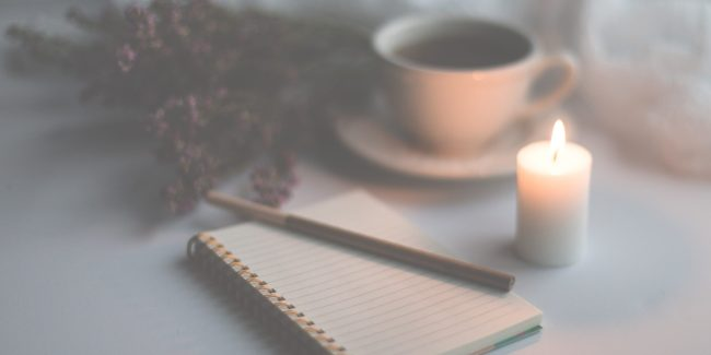 white note pad with pen on top, a small white lite candle, a small white cup of tea, and flowers on a white counter top.