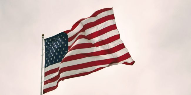 American flag waving with white cloud background.