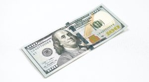 100 dollar bill laying face up on a white surface.