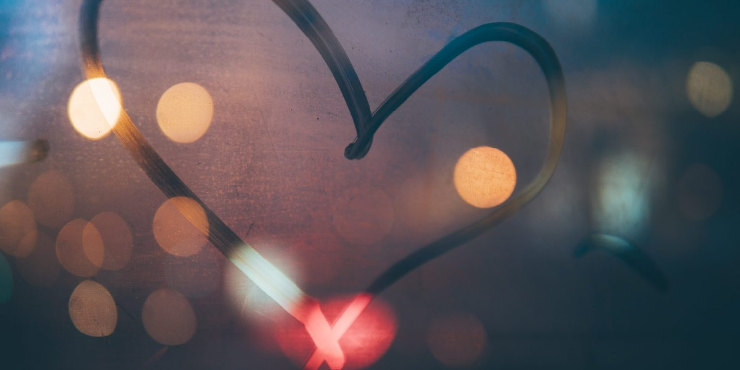 A heart made from the steam on a window with street lights in the background.