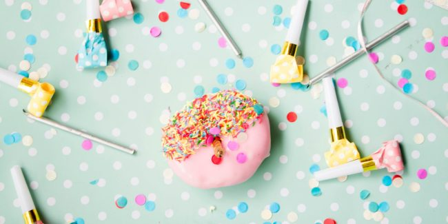 Flatlay of a pink donut with sprinkles and noise makers on a light blue background.