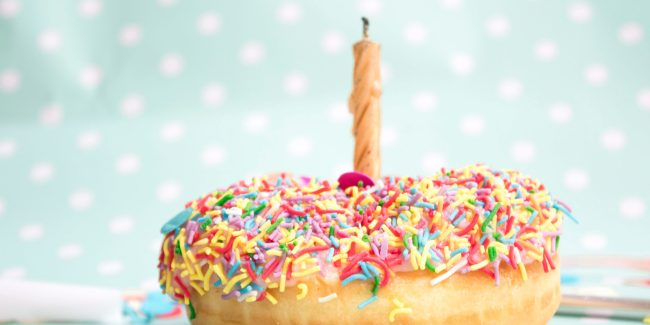 a glazed donut with multicolored sprinkles on top and a single candle standing in the middle.