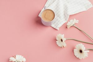 White flowers, next to a white coffee cup with tea and a white linen towel on top of a pink counter.