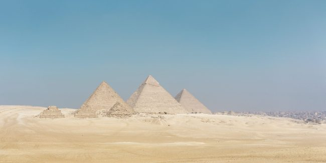 Pyramids off in the distance with a blue sky behind them.
