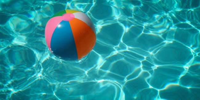 A multicolored beach ball floating in a swimming pool.