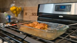 A clear Pyrex dish with enchiladas in it on top of a black stove.