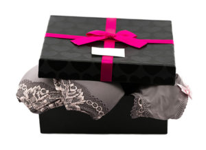 Woman lace lingerie in gift box decorated pink ribbon with bow
