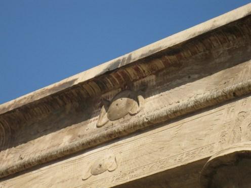 Le linteau de la porte d'accès au temple On distingue les deux cobras, symboles du nord, encadrant le disque solaire portant les ailes de vautour, symbole du sud