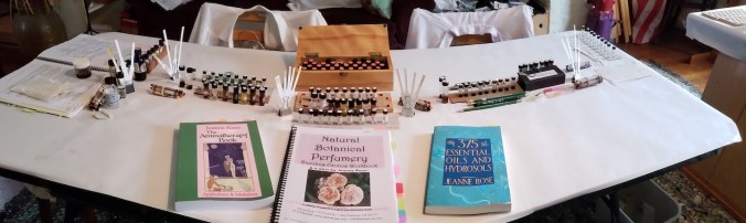 the home perfumery table showing textbooks, vocabulary of odor bottles, scent blotters and scents