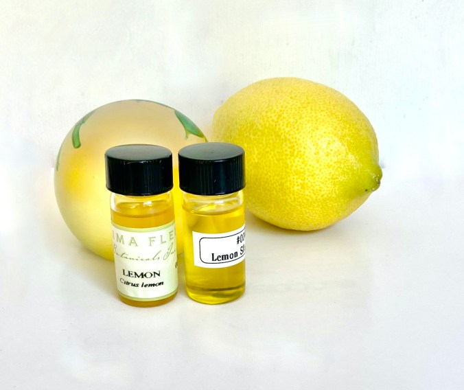Two bottles of Lemon oil plus a yellow paperweight and a perfect yellow Lemon.