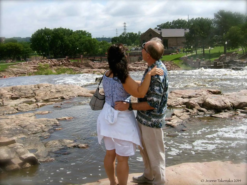 A couple standing next to a river, arm in arm
