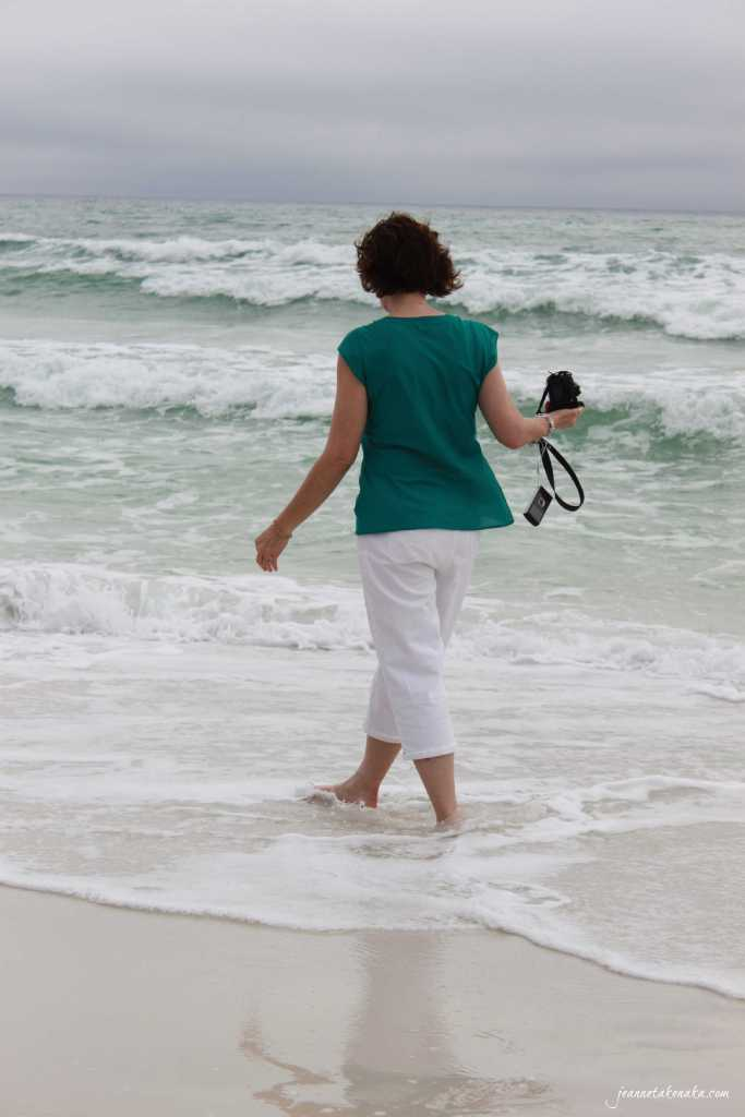 A woman walking in the shallows as waves roll onto shore