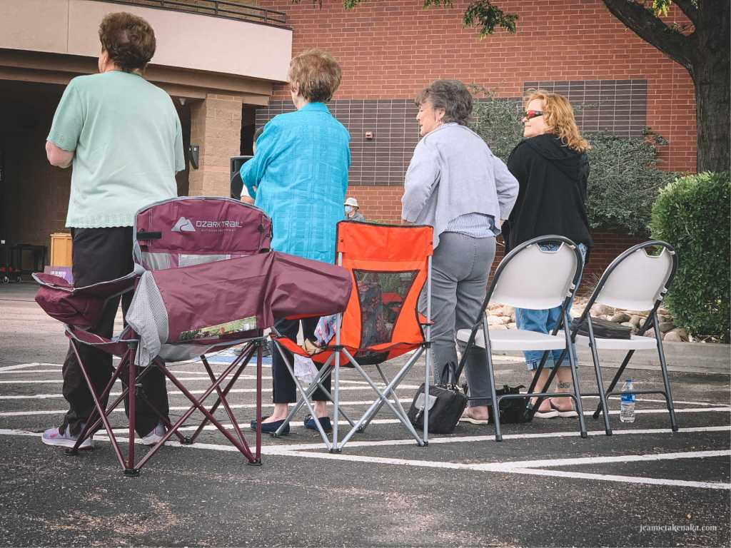 Four women worshiping at an outdoor church service, creating community with each other