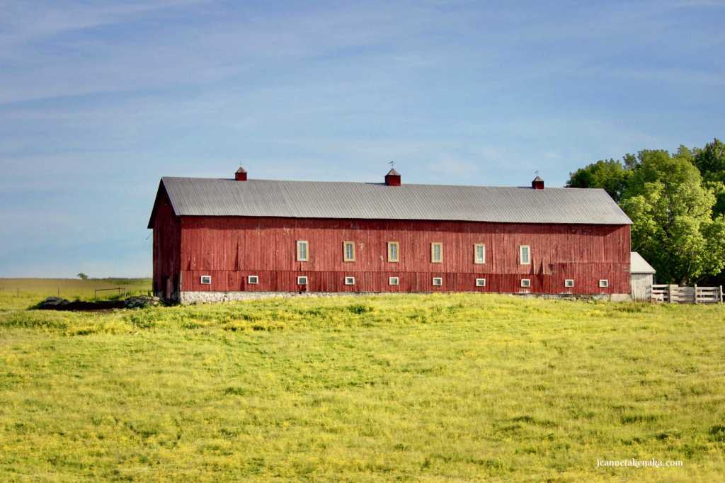 An image of a long red barn on a grassy knoll