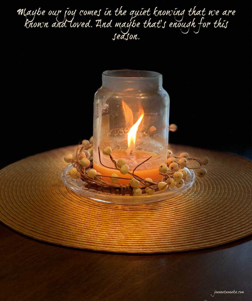 """A meme that says, """"Maybe our joy comes in the quiet knowing that we are known and loved. And maybe that's enough for this season."""" on a backdrop of a candle with a dancing flame."""