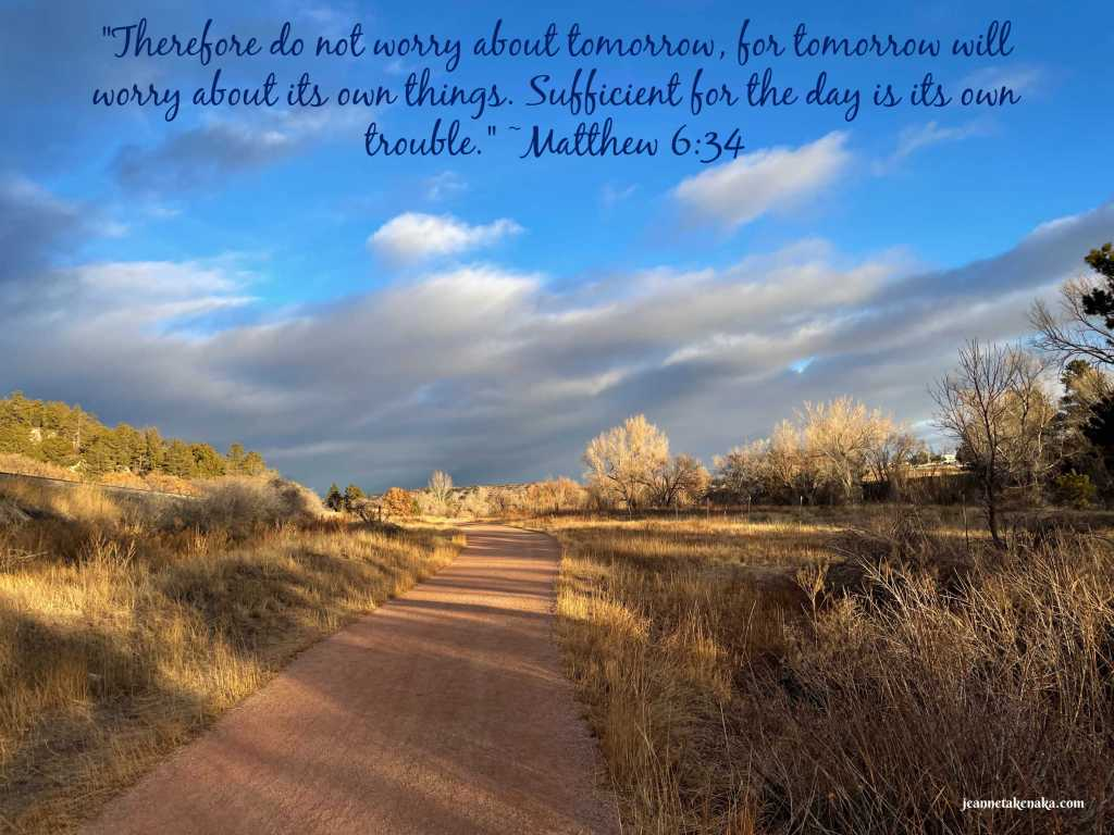 """A meme with the words: """"Therefor do not worry about tomorrow, for tomorrow will worry about its own things. Sufficient for the day is its own trouble."""" ~Matthew 6:34 on a backdrop of a shady path with sun shining on trees in the background"""