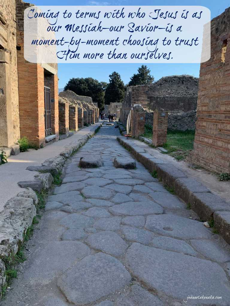 "A meme with the words, ""Coming to terms with who Jesus is as our Messiah—our Savior—is a moment-by-moment choosing to trust Him more than ourselves."" on a backdrop of a narrow cobblestone street"