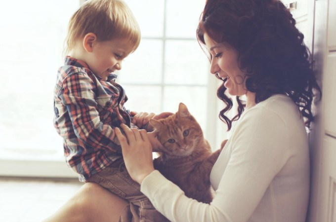 Mother with her baby playing with pet on the floor at the kitchen at home