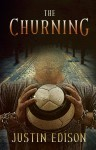 """Figure in chains holding a soccer ball before a cobblestone road, cover for """"The Churning"""""""