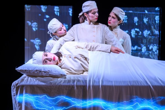 The two Penfields and Shapiro standing behind Mrs Gold on the operating table as an audience projection watches. An opportunity to capture brain functions through electrical stimulation. Production photo by Dahlia Katz.