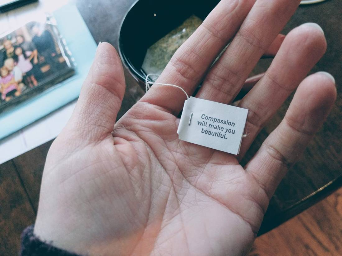 "Photo of hand holding tea bag label saying ""Compassion will make you beautiful."""
