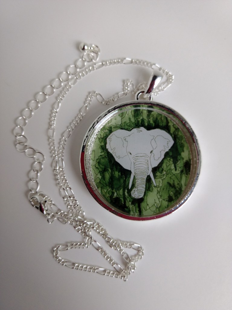 image of round silver necklace with white elephant and green background
