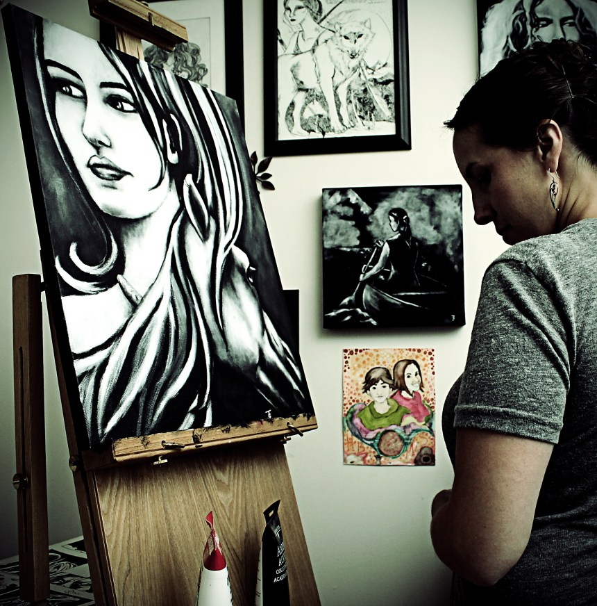 Female artist standing in front of painting on easel-Jeffcoat Art