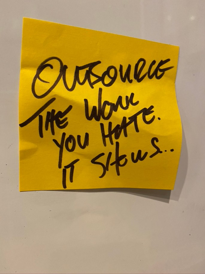 "Yellow post it note with the phrase ""outsource the work you hate, it shows"" written in sharpie marker"