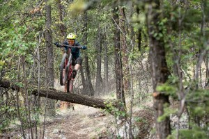 Jeff Kendall-Weed jumps over a log on his mountain bike