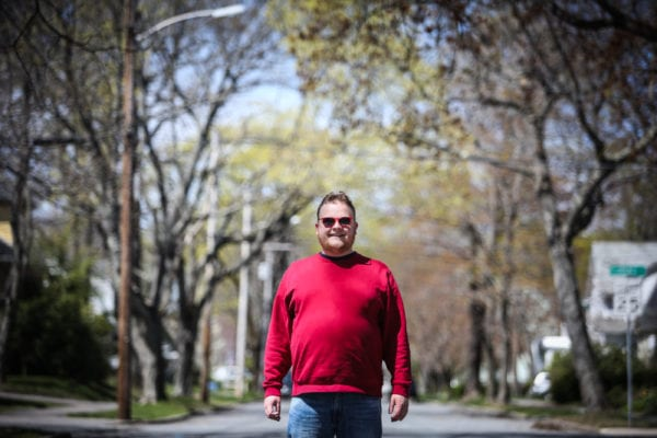 "PORTLAND, MAINE -- 05/04/17 -- Portland comedian Connor McGrath stands on the leafy street in Deering he's called home for most of his life. McGrath's Asperger's syndrome doesn't hinder his comedy, he said, ""It's just like being left handed."" Troy R. Bennett 