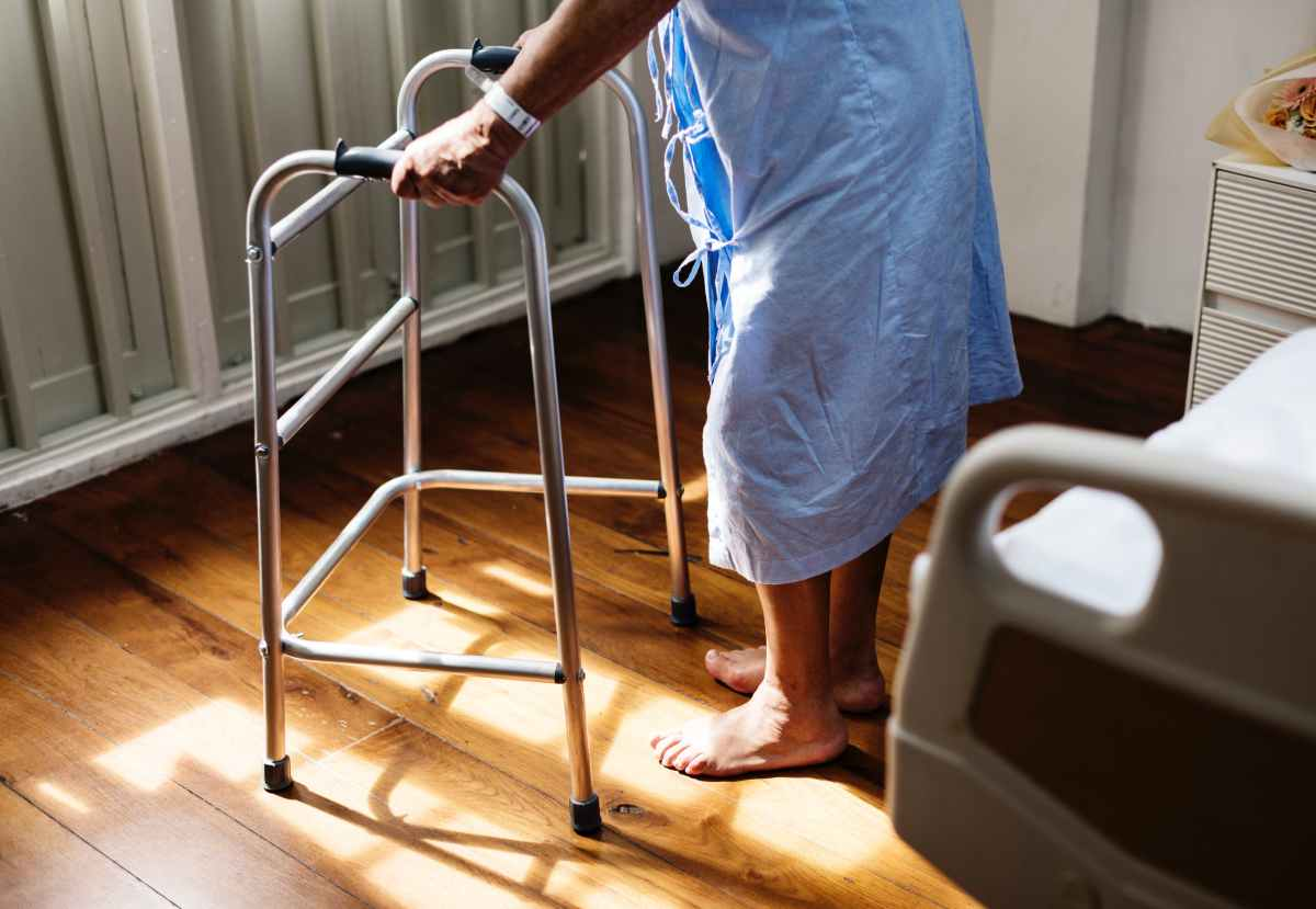 Older person, wearing a hospital gown, using a walker to get out of bed