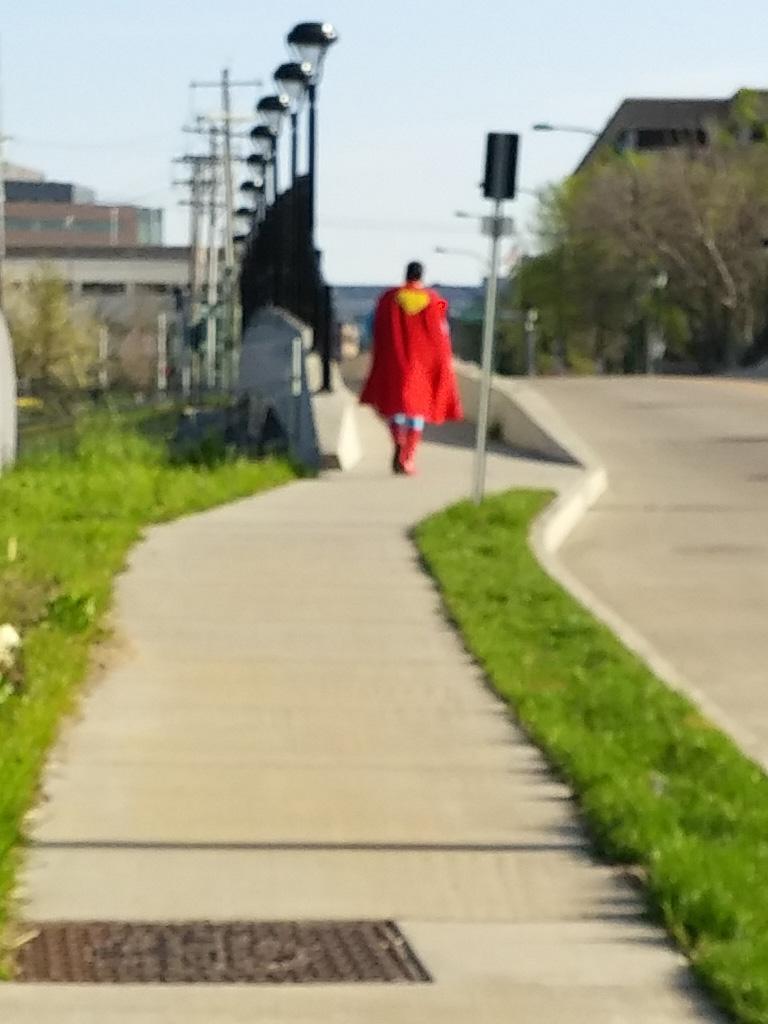blurry photo of man in Superman costume walking away down a sidewalk