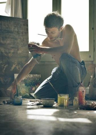 photo of a shirtless man kneeling on the floor and painting