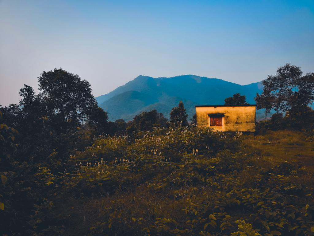 Photo of a small cabin in a grassy area with mountains in the background